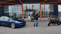 Tesla Model 3 яде бой от електрически мотоциклет
